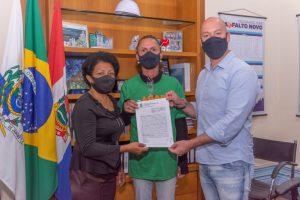 Prefeito Vinicius Claussen com Lucineia Silva, presidente da Associação de Moradores e Amigos do Caleme, e a gari comunitária Márcia da Costa Souza