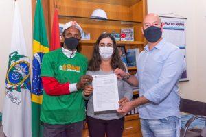 Rosana Martuchelli Nogueira, da Associação de Moradores e Pequenos Produtores de Microbacias Hidrográficas do Rio Formiga, Lúcios e Comunidades Vizinhas, entre o PrefeitoVinicius Claussen e o gari comunitário Edson Gomes